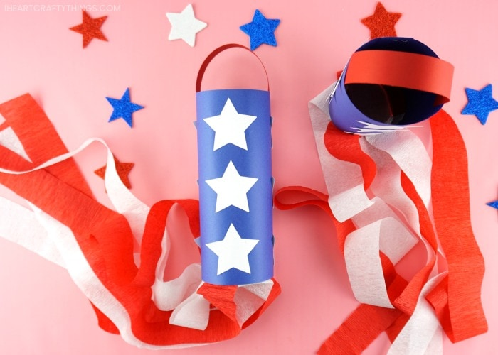 One patriotic windsock laying flat and one standing up on a pink background with glitter star stickers scattered around.