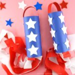 Two red, white and blue patriotic windsocks laying flat on a pink background with glitter star stickers scattered around.