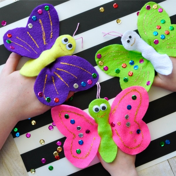 Square image of three children playing with butterfly finger puppets
