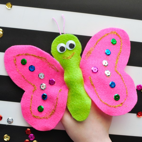 Child playing with a pink and green felt butterfly puppet.