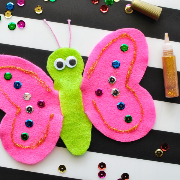 Square close up image of decorating butterfly finger puppet with sequins and glitter glue.