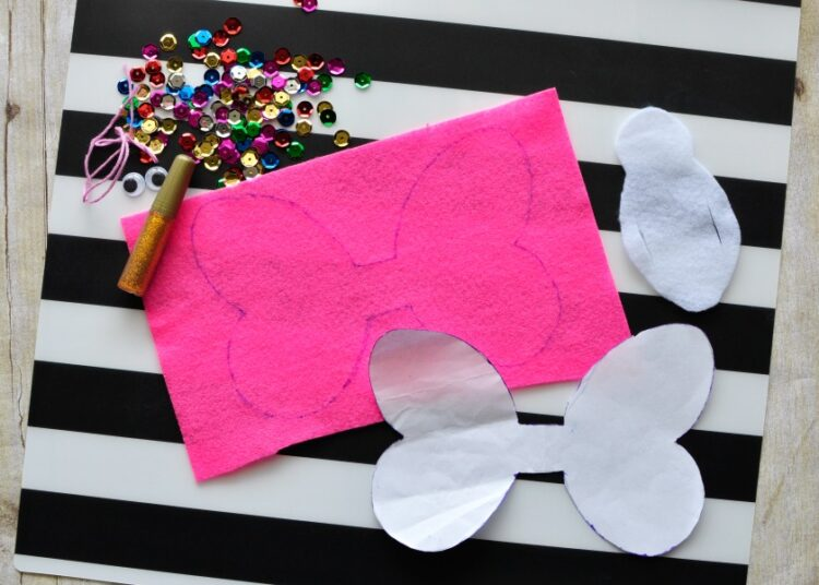 supplies for making butterfly finger puppet laying out on a black and white striped placemat.