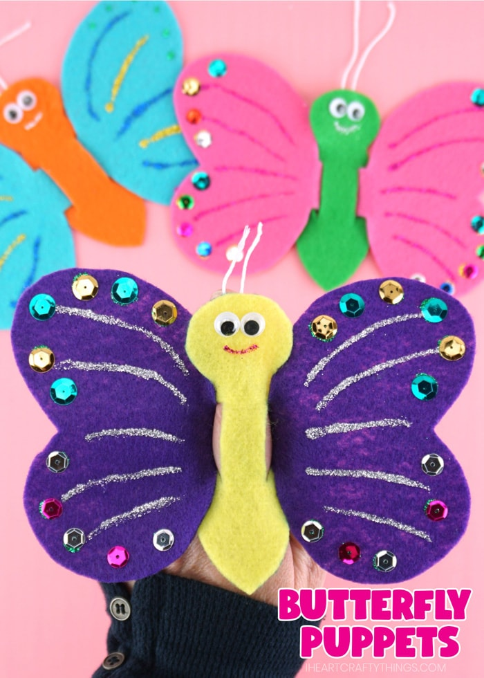"""Vertical close up image of someone playing with butterfly finger puppet with two puppets out of focus in the background and the words """"Butterfly Puppets"""" in the bottom right corner."""