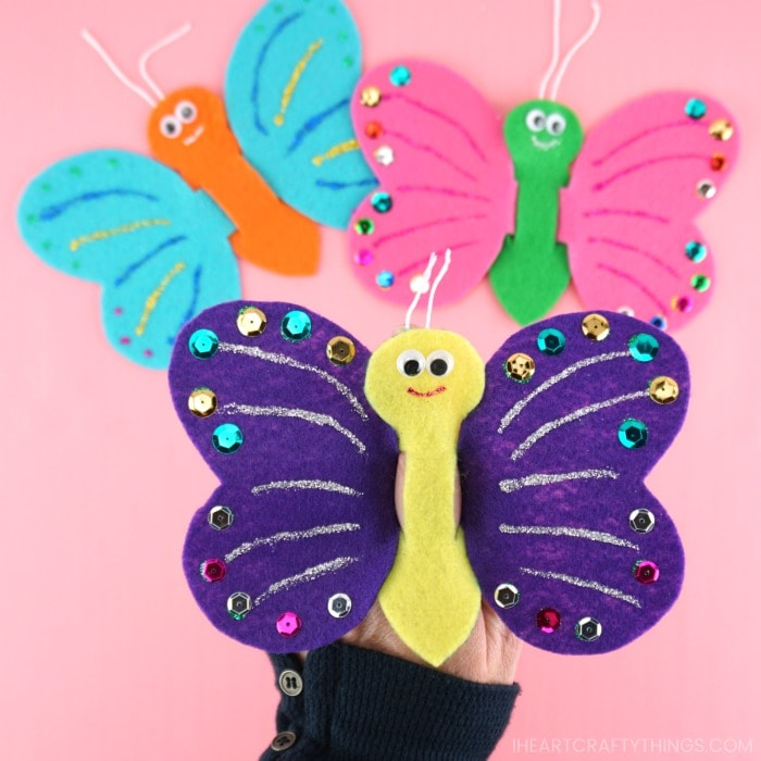 Close up image of someone playing with the butterfly finger puppet with two more puppets out of focus in the backrground.