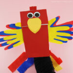 Adult with their hand inside the paper bag parrot puppet showing how to move the beak open and closed.