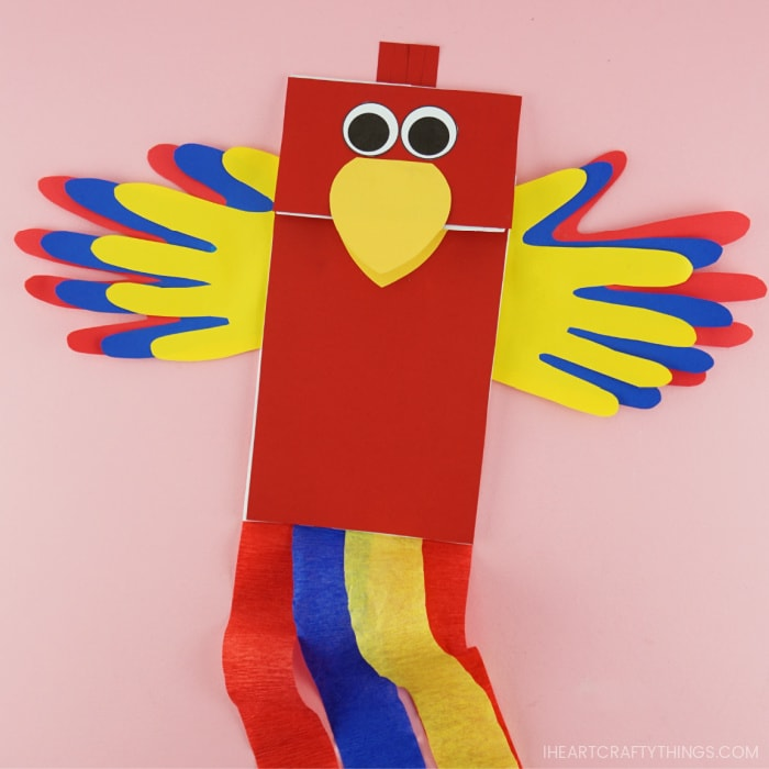 Completed paper bag parrot craft laying flat on a pink background.
