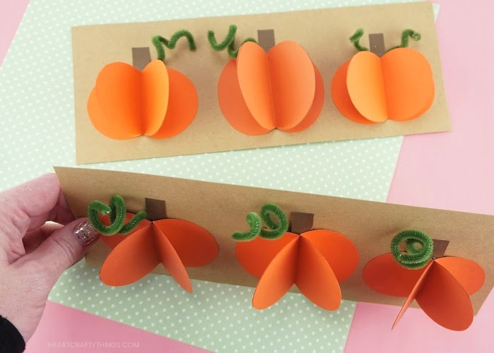 Two paper pumpkin crafts with adult holding one up to see a downward angle of the 3d pumpkins.