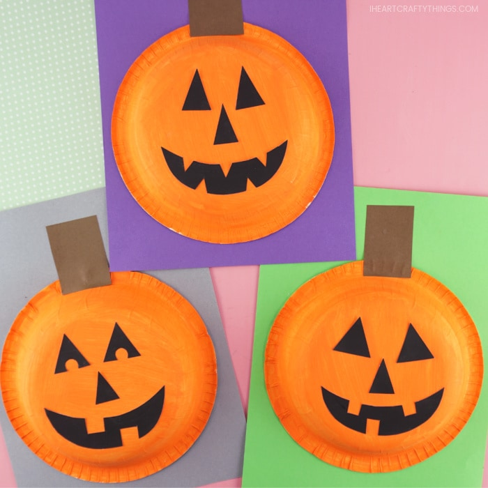 Square image showing three completed paper bowl pumpkin crafts laying with each other on a pink background.