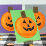 Paper bowl pumpkin craft propped up on an angle in center with two more pumpkin crafts out of focus in the background.