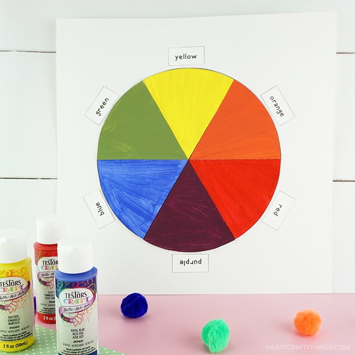 Finished color wheel craft propped against a white shiplap background with Testors red, yellow and blue acrylic paint bottles and craft poms sitting in front of the artwork.