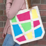 A girl standing sideways with the geometric painted canvas bag over her shoulder.