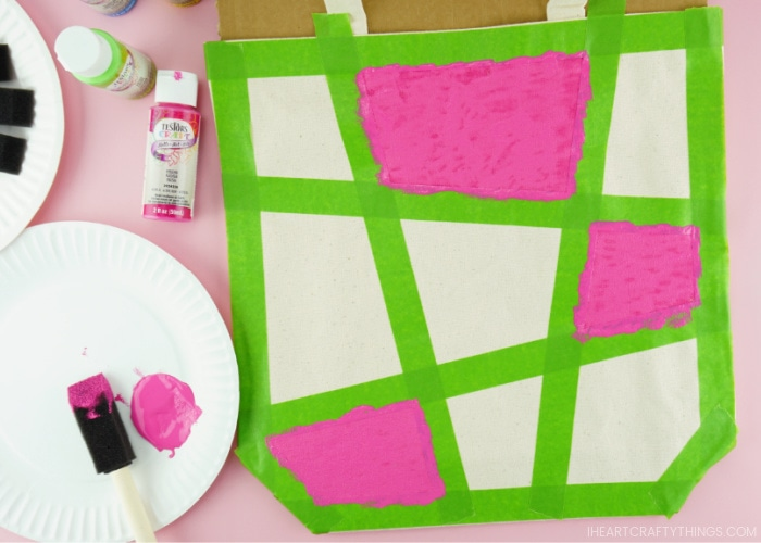Close up image of canvas bag with three of the taped off shapes painted with pink acrylic paint. Paper plate with pink paint and spongebrush laying in the bottom left corner.