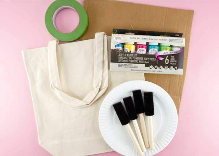 Materials needed to make the painted canvas bag laid out: canvas bag, cardboard, acrylic paint, painters tape, paper plates and sponge paintbrushes.