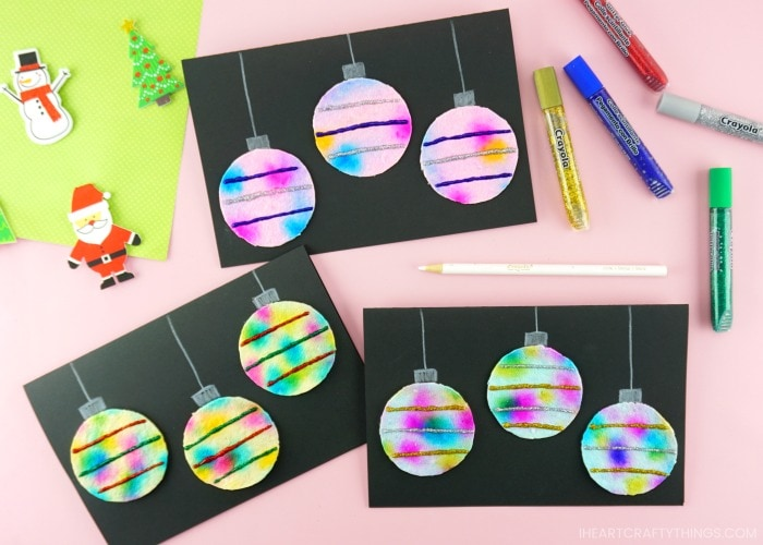 Horizontal image displaying three folded hanging ornaments Christmas cards on a pink table with white colored pencil and glitter glue scattered around the cards.