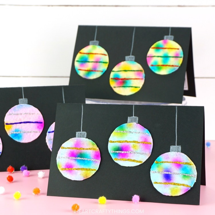 Three DIY hanging ornaments Christmas cards on display on a pink table with a white shiplap background. The card in front is in focus and the ones in back are out of focus.