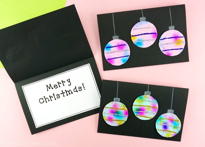 """Two hanging ornaments Christmas cards laying flat on a pink background and one laying open with the message """"Merry Christmas"""" on the inside."""