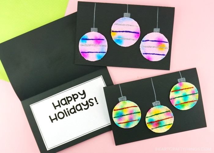 """Close up image of three homemade Christmas cards with one laying open showing """"Happy Holidays"""" on the inside of the card."""