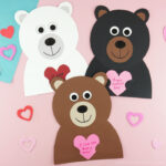 Polar bear, black bear and brown bear Valentine Craft all touching and laying next to each other on a pink background with hearts scattered around.