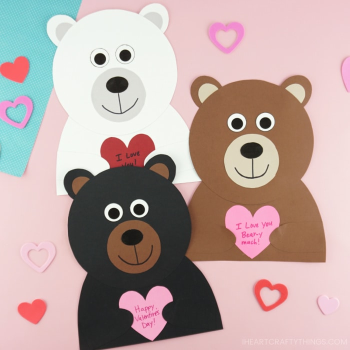 Polar bear, brown bear and black bear Valentine crafts laying next to each other on a pink background with heart stickers scattered around them.
