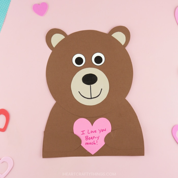Close up image of finished bear Valentine craft laying on a pink background.