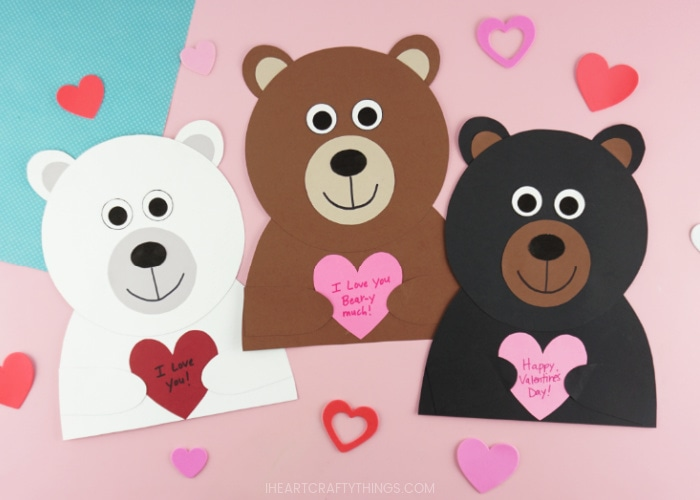 Horizontal image showing a polar bear, brown bear and black bear Valentine craft all laying next to each other on a pink background with heart stickers scattered around them.