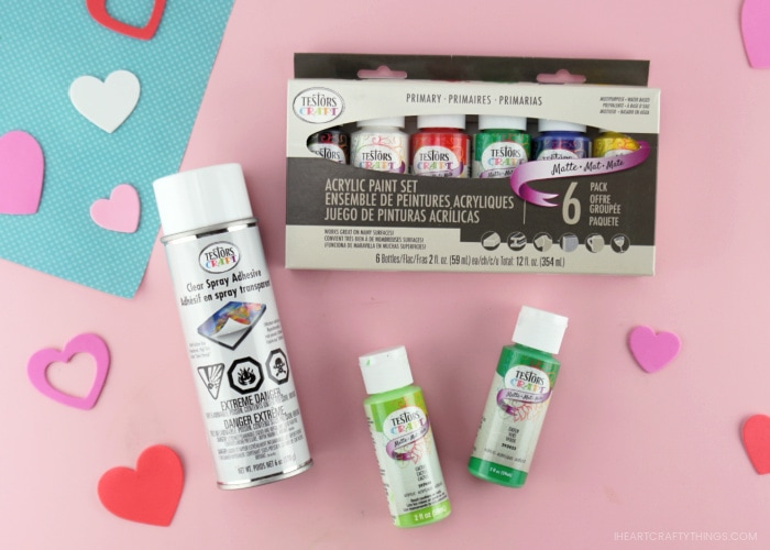 Assortment of Testors Craft acrylic paints and Testors spray adhesive laying down on a pink background with heart stickers scattered around.