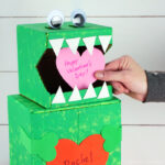 Close up image of person placing a heart Valentine inside the mouth of the dinosaur Valentine box.