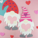 Two Valentine paper gnome crafts laying side by side on a pink background with heart stickers scattered around.