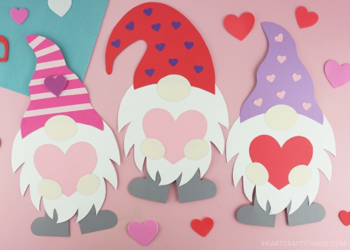 Three paper Valentine gnomes laying next to each other on a pink background with heart stickers scattered around.