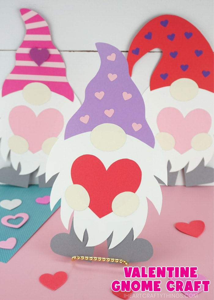 """Vertical image of three Valentine gnome crafts with one in front in focus and two in the back out of focus. The words """"Valentine Gnome Craft"""" is in the bottom right corner."""