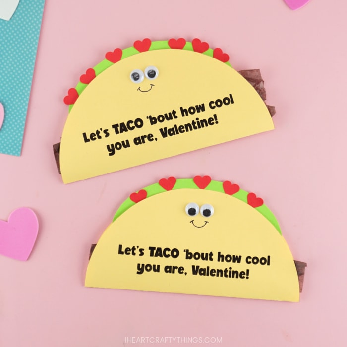 Close up square image of two taco Valentine's Day cards on a pink background laying one on top of the other.