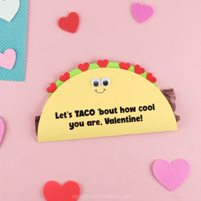 Close up image of DIY taco Valentine's Day card laying on a pink background with heart stickers scattered around.