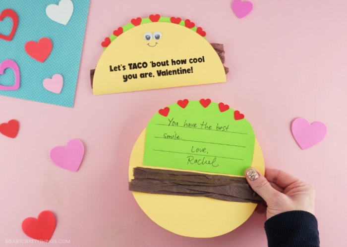 """Image showing an adult holding open the taco Valentine's Day card showing the message written on the inside that reads """"You have the best smile! Love, Rachel""""."""