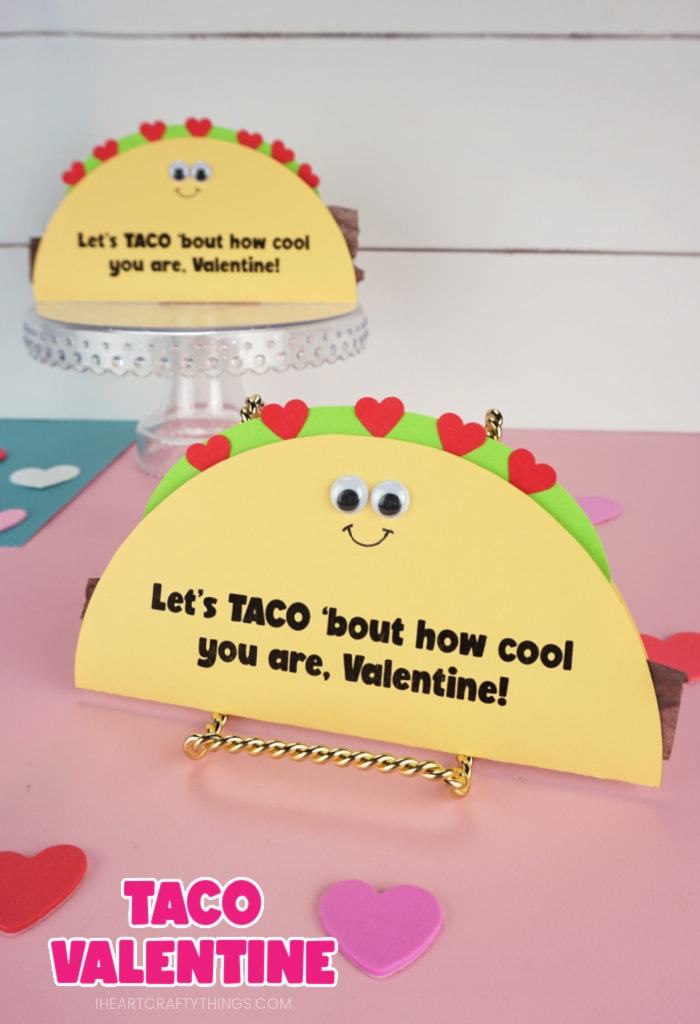 """Vertical image of two taco Valentine's Day cards propped up with the front taco up close and in focus and the back taco out of focus. Text """"Taco Valentine"""" in the bottom left corner of image."""