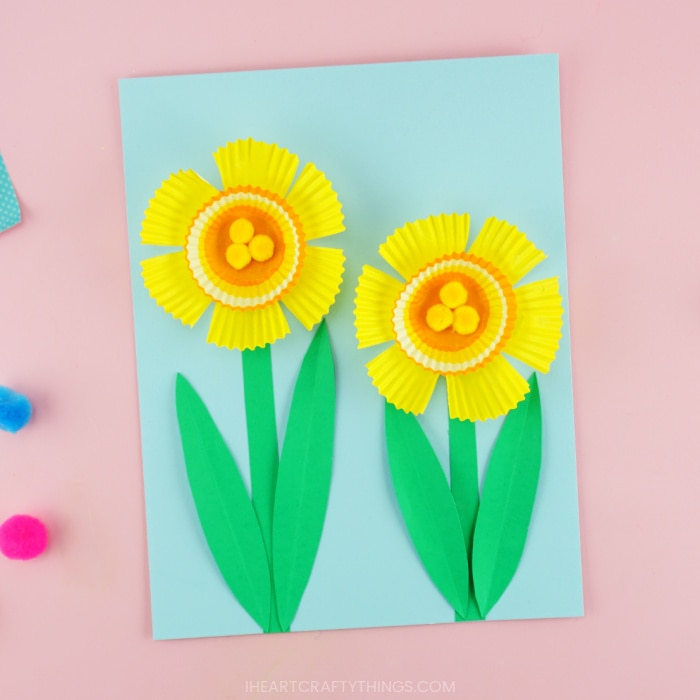 Finished daffodil craft for kids made out of cupcake liners and paper laying on a pink background.