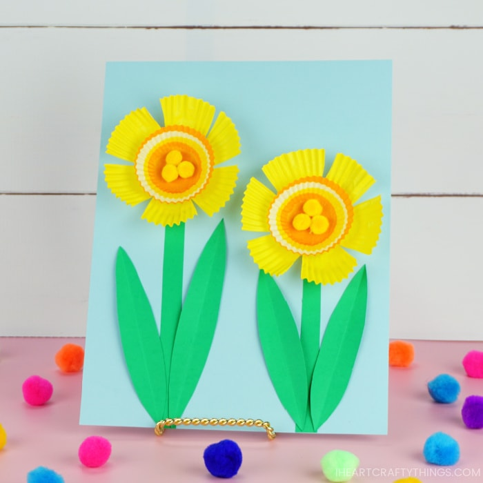 Cupcake liner Daffodil craft on a stand, sitting on a pink table with colored poms scattered around and a in front of a white shiplap background.