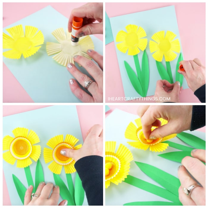 Four image collage showing how to glue the yellow cupcake liners and green stem and leaves onto the blue cardstock paper, and how to glue the mini cupcake liners and small yellow poms on the inside of the flower.