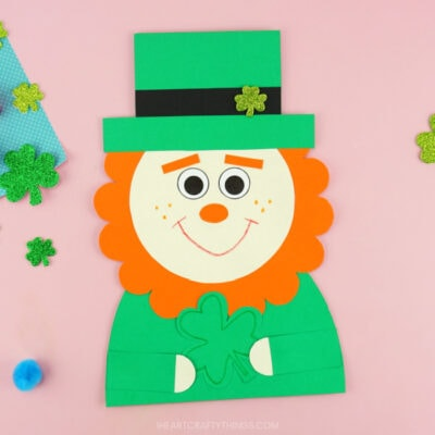 Completed leprechaun paper craft centered in the photo and laying on a pink background with glittery shamrock stickers and colored poms scattered around.