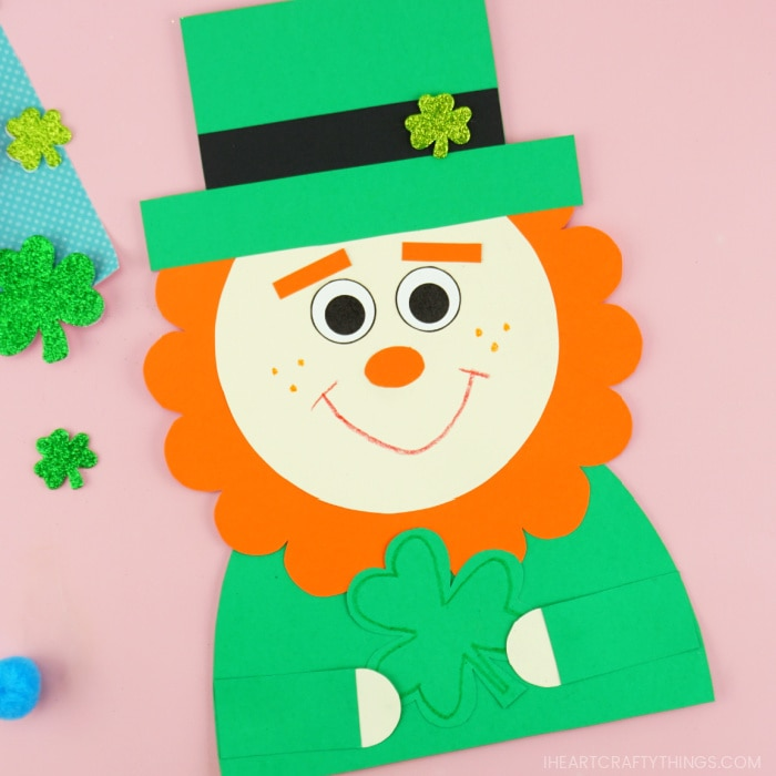 Close up image of leprechaun paper craft laying on a pink background.