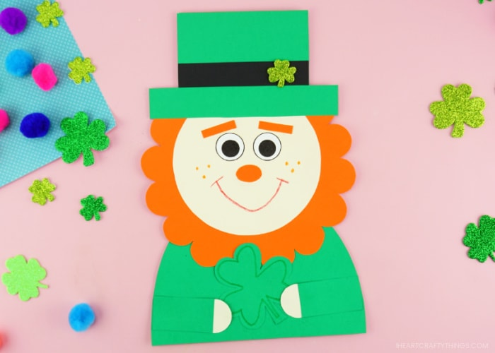 Horizontal image showing the finished leprechaun craft in the center of the photo laying on a pink background with glittery shamrock stickers and colored poms scattered around.