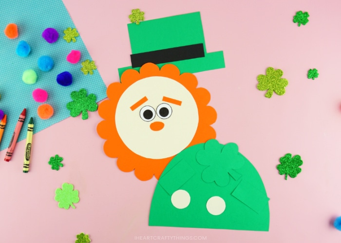 Each of the pieces from the leprechaun craft template cut out and laying on a pink background with shamrock stickers, colored poms and a few crayons scattered around them.