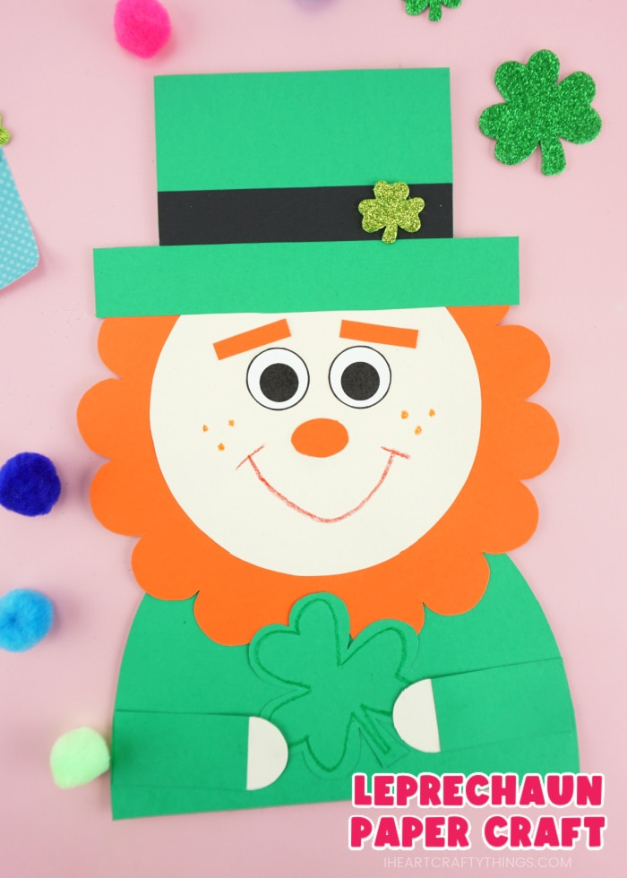 "Close up vertical image of a leprechaun paper craft with colored poms scattered around it and the words ""Leprechaun Paper Craft"" in the bottom right corner."