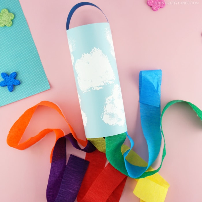A kid-made rainbow windsock craft laying down flat on a pink background with the rainbow strips flowing out of the bottom of it in different directions.