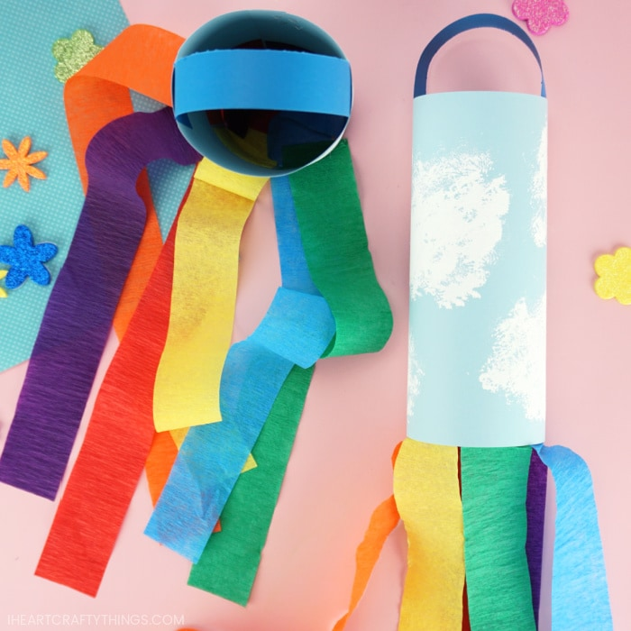 Two rainbow windsocks with the one on the left laying flat and the one on the left standing up with the rainbow strips flowing out of the bottom of it.